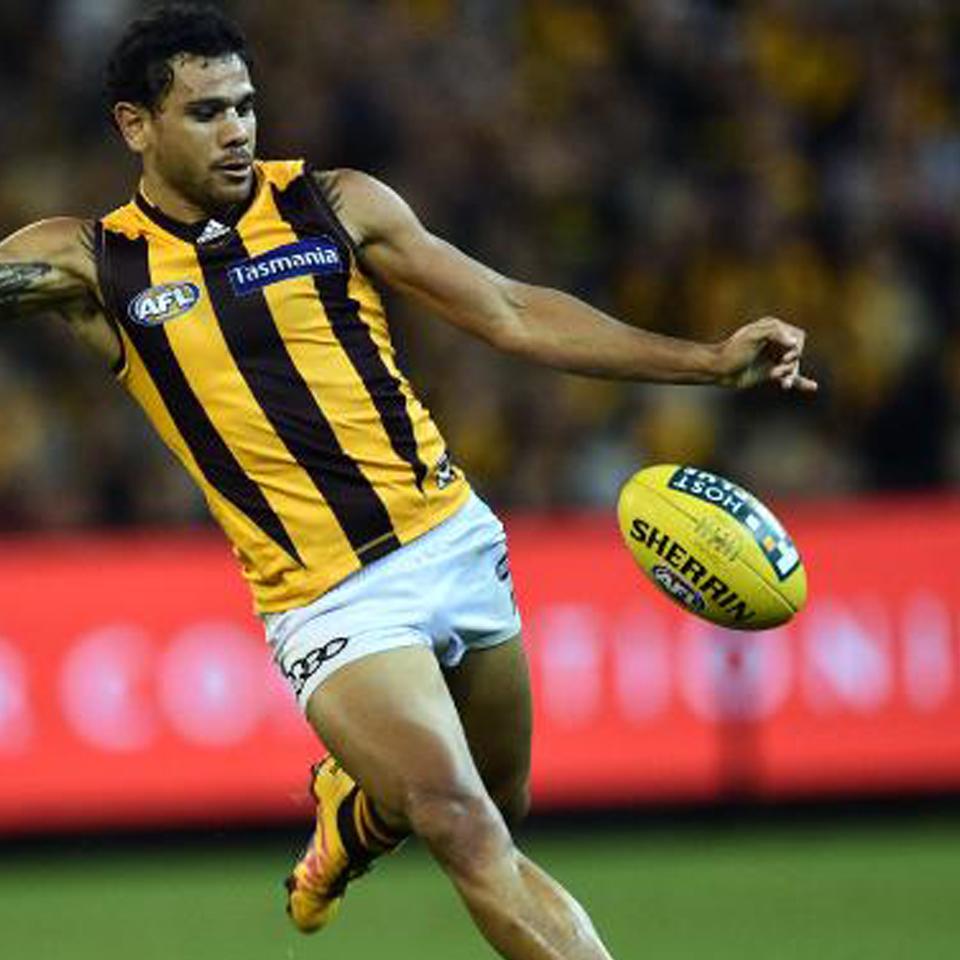 AFL Player kicking ball